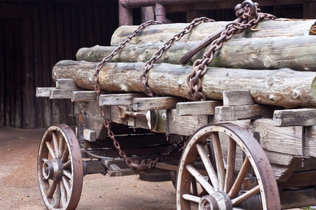 hub: Old wagon with logs secured with chains Stock Photo