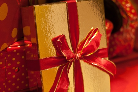 Present wrapped in gold paper with a red bow Stock Photo
