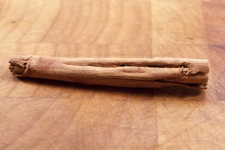 A single cinnamon stick on a wooden bench Stock Photo