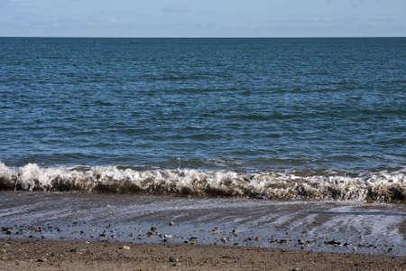 beach shingle: Onde che si infrangono su una spiaggia di ciottoli