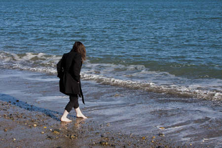 Young lady barefoot on the sea shore on a cold day