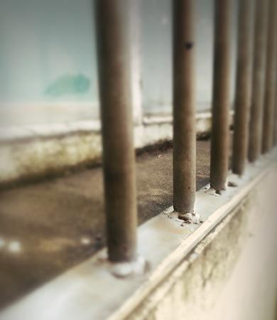 metallic: Rusting metal bars in front of window