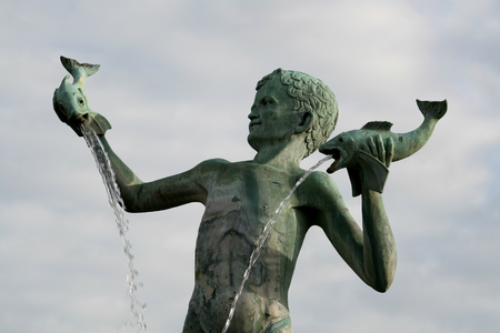 Bronze fountain of a young boy holding fish with sea lions around the base, St Michaels Fountain Square, Braintree, Essex, England  Stock Photo
