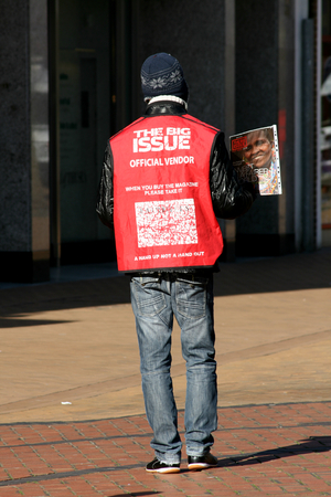 Big Issue magazine seller, pedestrian shopping precinct, High Street, Chelmsford, Essex, England Editorial