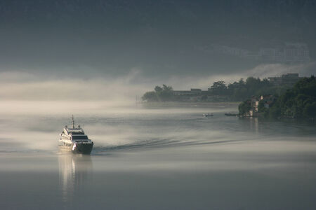 Boat emerges from early morning mist, Bay of Kotor, Montenegro photo