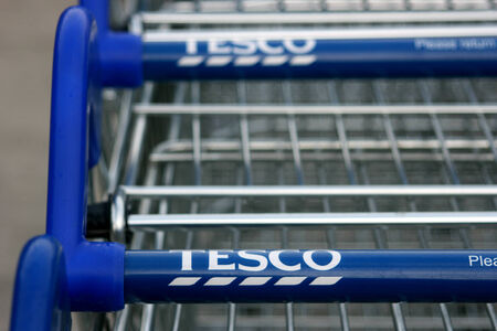 Tesco supermarket store shopping trolly handle with white on blue logo