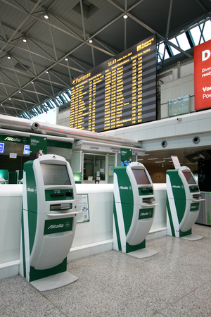 Alitalia self check in machines and departure board in Terminal 1 of Fiumicino Airport in Rome, Italy Editorial