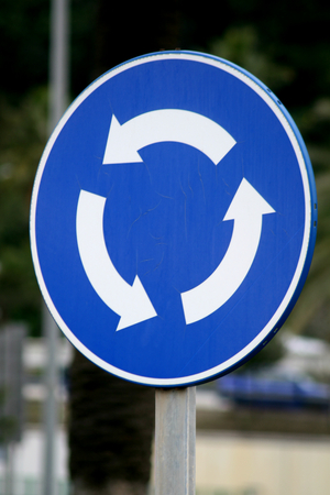 White arrows on blue background of roundabout direction sign, Barcelona, Spain