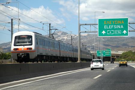 adjacent: Suburban train on railway line adjacent to motorway, Athens, Greece