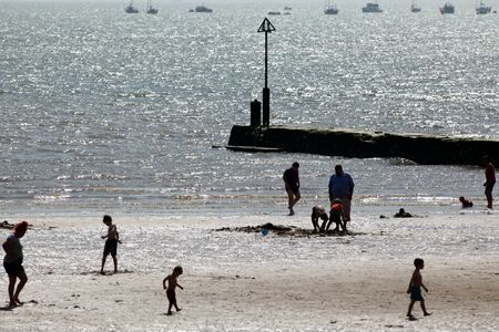 essex: Silhouetted people enjoying the beach, Clacton, Essex