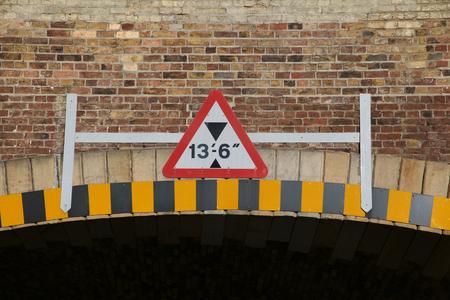 Height warning sign on bridge under railway line at Chelmsford Railway Station, Essex