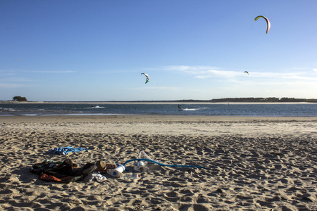 kite surfing: Kite surfing equipment and clothing on a Queensland beach with kite surfers in the background.