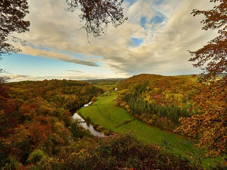 River Wye in Autumn Colours - Panoramic view of the River Wye with trees in autumn colours of orange and gold with a sky illuminated by a setting sun. Imagens