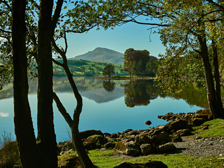 Bala Lake or Llyn Tegid, Bala, Snowdonia. Picturesque landscape scene of Bala lake with clear blue sky, shoreline and mountains reflected on the water. In the distance is the ridge of Aran Benllyn with the peak of Aran Fawddwy on the skyline.