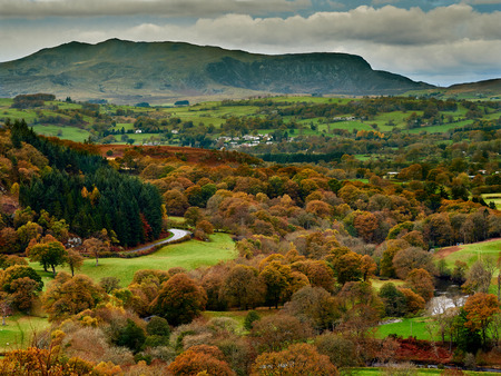 Upper River Dee Valley and Arenig Fawr in Autumn  Fall. A picturesque landscape scene of the upper river Dee valley with trees in autumn  fall orange and gold colours. Situated near Bala it is an isolated mountain peak with splendid views of Snowdonia. Imagens