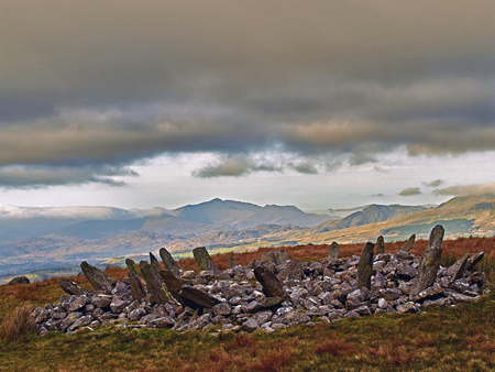 Bryn Cader Faner Cairn Circle. This ancient monument is a combination of a burial mound with a stone circle of slabs sticking out like a crown of thorns. Set in a scenic landscape with the sea to the south and Snowdon to the north.