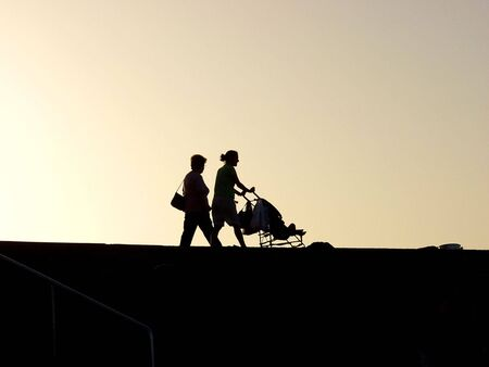 hectic life: a woman walking whit child and grandmother at sunset Stock Photo