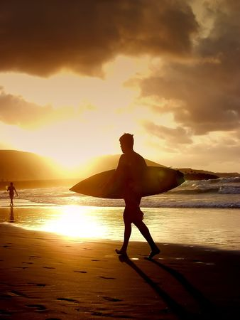 Young boy surfer wlaking on the sand whit his surf board at sunset photo
