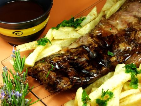 Barbequed  back ribs with french fries on a plate.