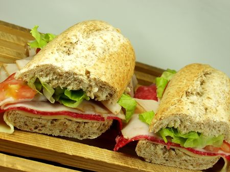 hoagie: two middle salami sandwich on wooden surface