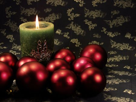 customs and celebrations: detail green christmas candle on blue decorated background  and red balls