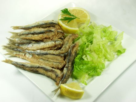 anchovy fish: fried anchovy fish on white platter whit salad, spanish tapa Stock Photo