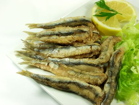 anchovy fish: fried anchovy fish whit salad on white platter, spanish tapa.