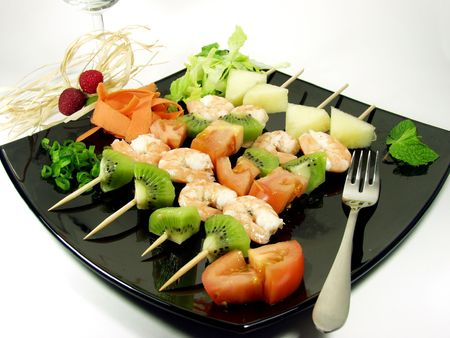 snacks of shrimps whit differents fruits on black platter photo