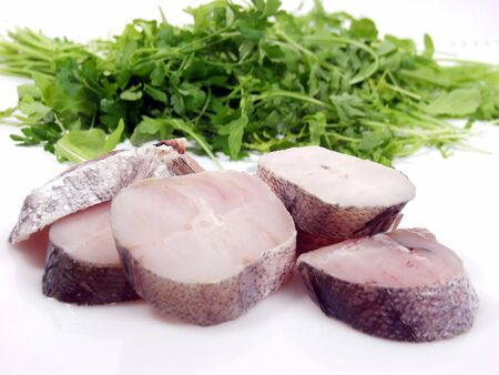 hake: Slices of fresh hake on white background and green salad Stock Photo