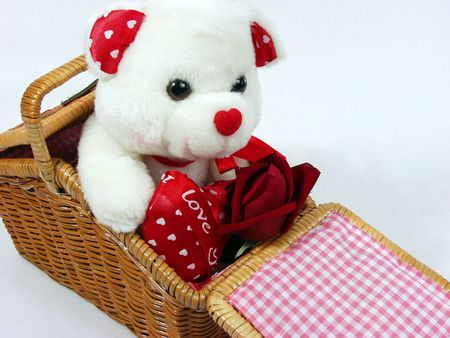 Teddy bear with red valentine heart on red background with red rose on hand photo