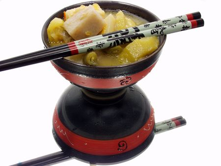scrumptious: a bowl of chinesse food with reflection on a mirror and chopsticks