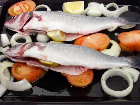 two fresh sea bass ready for cook on oven  with tomatoe and onions photo