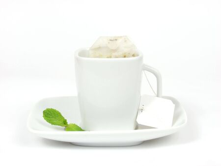 robustness: pure white tea cup with mint leaves on white background