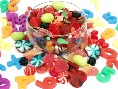 Colorful pastel candy and play numbers on glass bowl