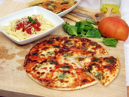 products of italian cucine with macaronni on tomato sauce and tasty pizza Stock Photo