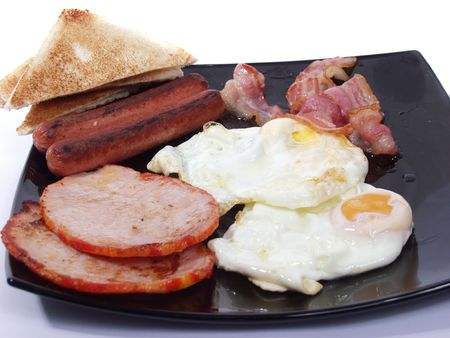 scrambled: platter of scrambled eggs with bacon sausages and toast bread Stock Photo