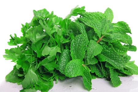 a bunch of fresh green mint and parsley on pure white