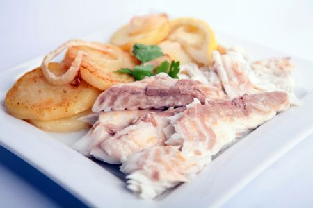 gilthead bream: Gilthead Bream fish cooked with potato slices in a white dish Stock Photo