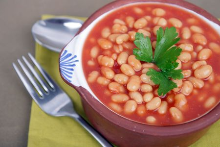 tasty tomato sauce beans on brown bowl with spoon photo