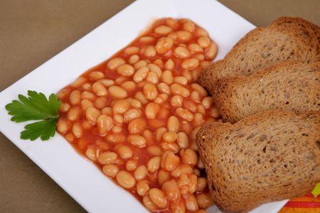baked beans: tasty tomato sauce beans on white platter with toast