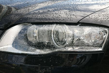 head lights of a sport black car with drops of rain photo