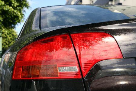 back lights of a sport black car in blue sky photo