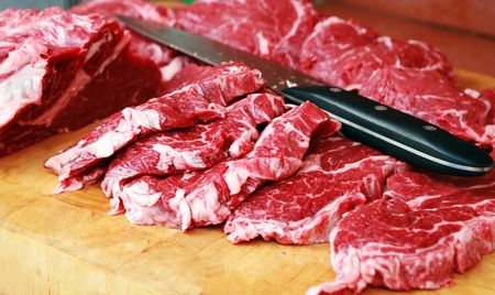 fresh beef on wooden board with knife