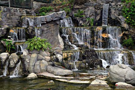 chute d'eau dans le jardin de ville avec des usines et des fleurs Banque d'images - 860637
