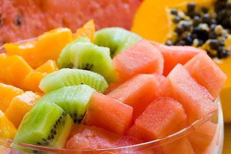 fresh and sweet fruit salad on glass bowl and fruits background photo