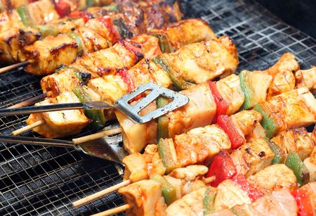 cooking chicken with pepper on outdoor barbecue photo