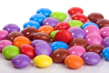 close up of sweet smarties on white background