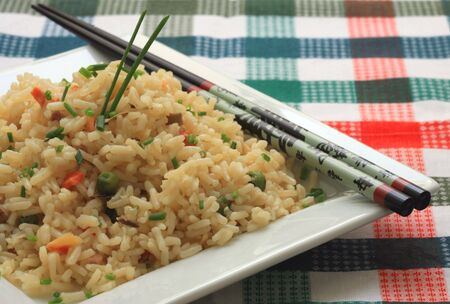 A plate of oriental fried rice with vegetables and chopsticks