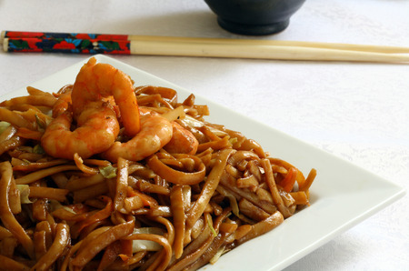 a white platter with stir fry noodles with prawn and vegetables Stock Photo