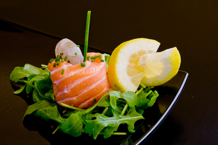 fresh raw salmon roll with a praw and rockets leaf and lemon